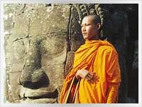 cambodian buddhist monk standing next to a giant head of the future buddha at Angkor Wat in Cambodia
