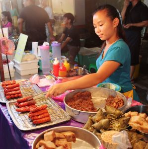 Image of malaysian-girl-selling-local-snacks-at-the-night-street-food-in-malacca-malaysia-98853109
